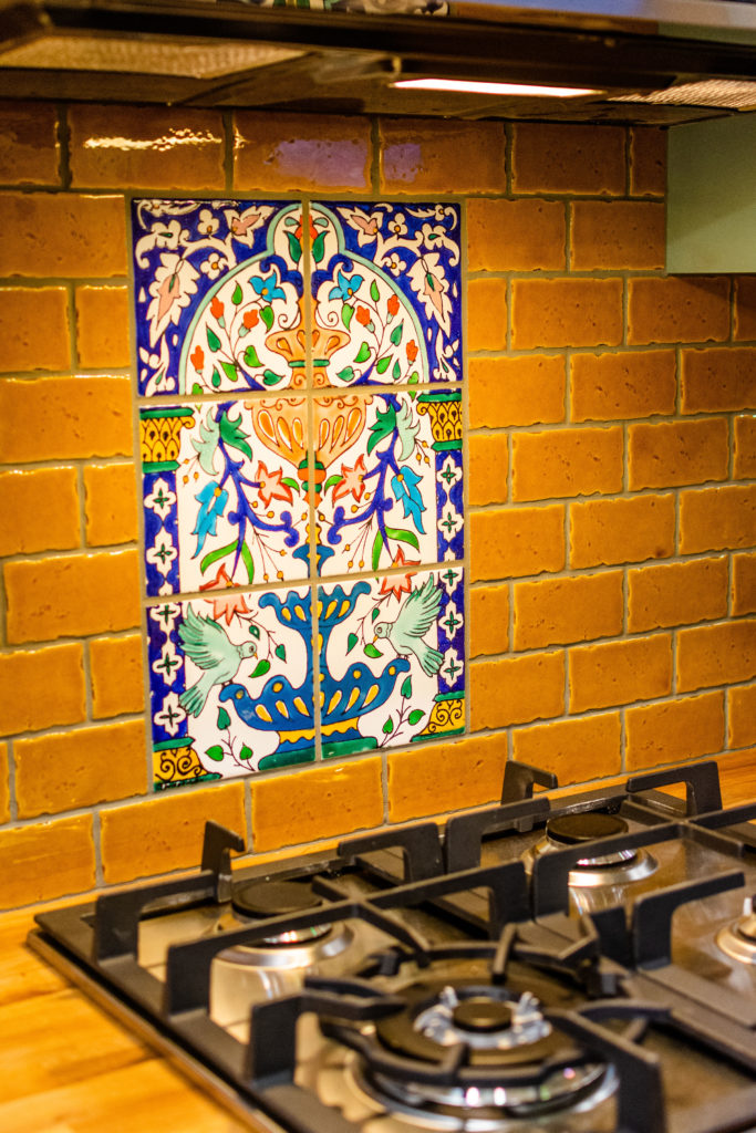 Carries tiny home closeup of kitchen tile work with blue french botanicals and brick background