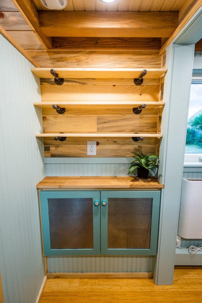 Carries tiny home view of storage nook by bath cabinets below and open shelving above