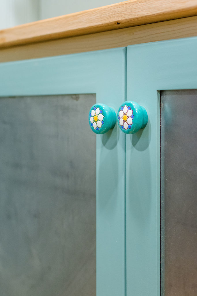 Carries Tiny Home closeup of cabinet pulls, aqua with hand painted daisies metal cabinet fronts framed with aqua painted wood