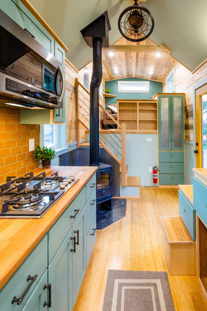 Tiny Home view with partial of kitchen and stairs, looking toward the goose-neck living room - wood stove and stairs