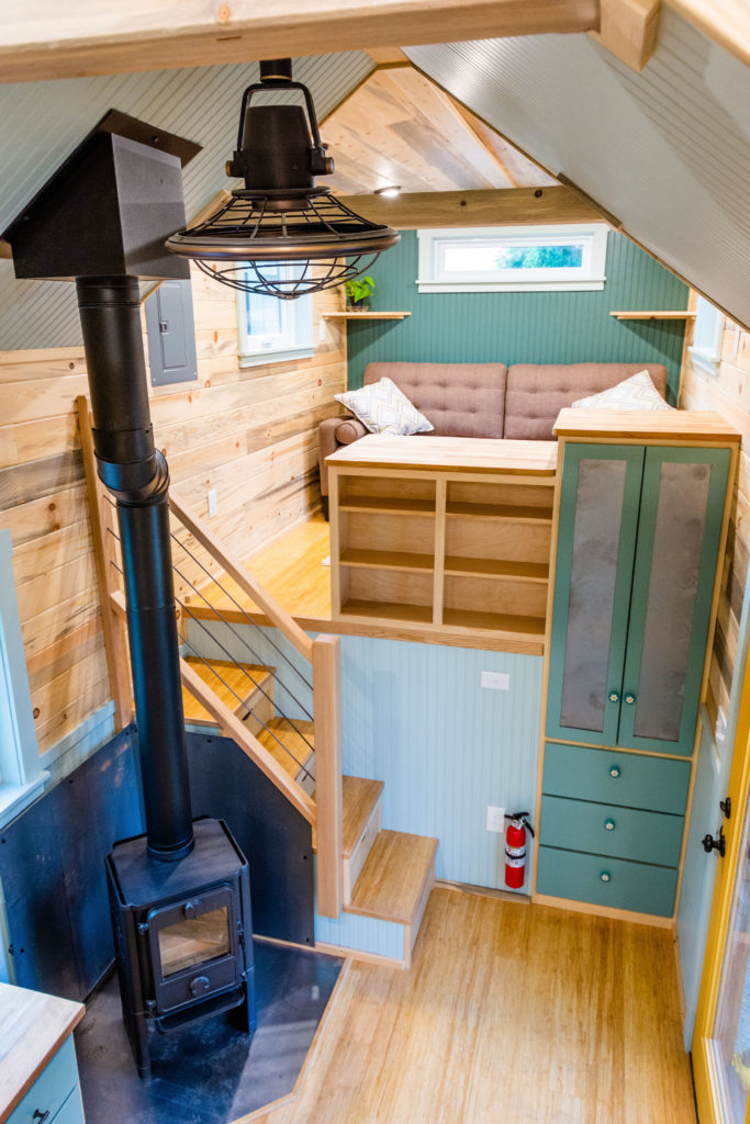 Tiny Home view of woodstove, stairs, and living room on the goose-neck with fan above