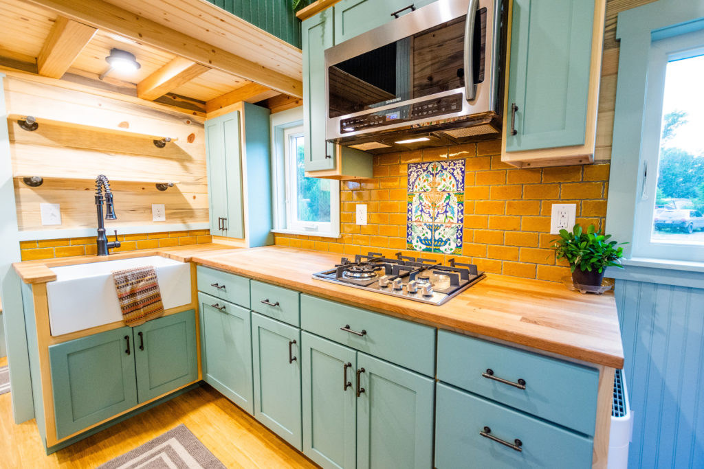 carries tiny home view of kitchen with farm house sink cabinets, open shelving and convection oven above 4 burner gas cooktop